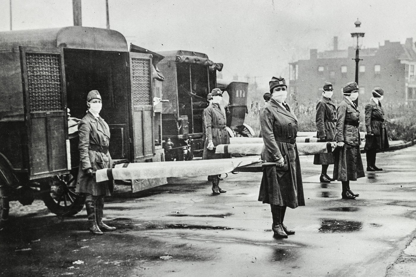 1918 influenza epidemic St. Louis Red Cross Motor Corps personnel wear masks as they hold stretchers next to ambulances in preparation for victims of the influenza epidemic in October 1918. (Library of Congress)